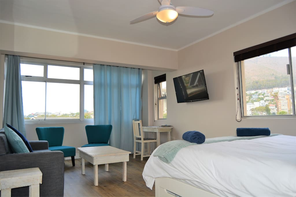 Comfortable queen bed with TV on swing arm so you can watch TV from the bed or couch plus great big windows looking on to the mountain and Green Point park