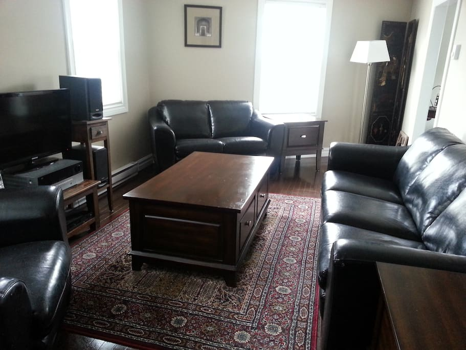 Living room with black leather sofa, chair, loveseat, new coffee table and end tables, tasteful art, flat screen cable TV, wireless internet throughout home. Doors to laundry room and downstairs rooms.