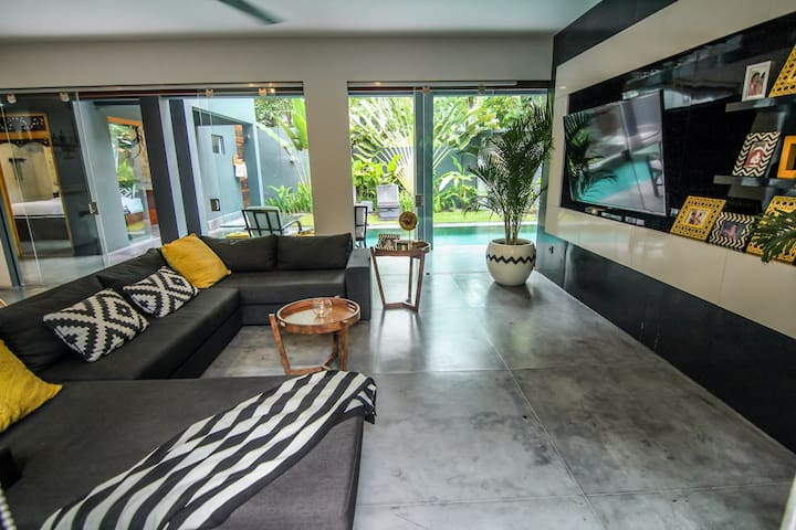 Living/dining room has direct pool access and  can be fully enclosed for air conditioning or opened up to enjoy cool breezes