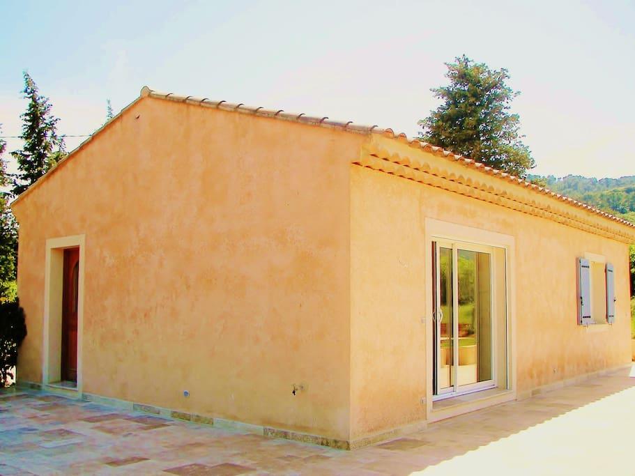 Vue ouest de la villa, une grande baie vitrée et la porte d'entrée sur la gauche. Vue sur la terasse en pierre posée en opus Romain