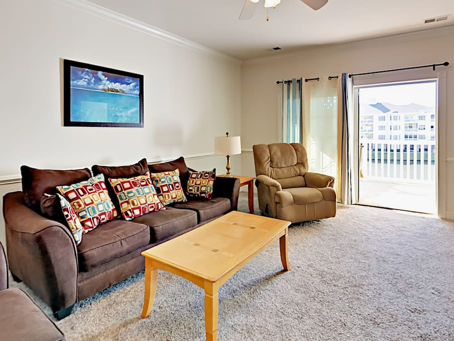 The living room has plenty of comfy seating and views of the pond and golf course.