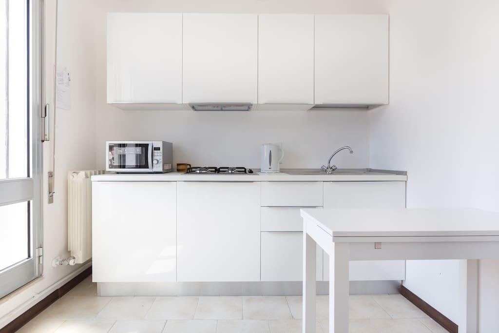 Cucina con microonde, lavatrice, frigo, fornalli | Kitchen with kitchenware, microwave, fridge and stove