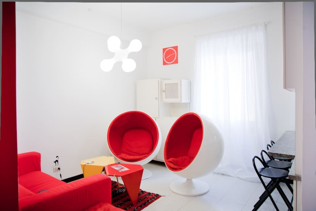 The living room has two Ball Chairs by Eero Aarnio. Light is by Cundalini. ARCO by Flos. and an old Italian Madia to complete