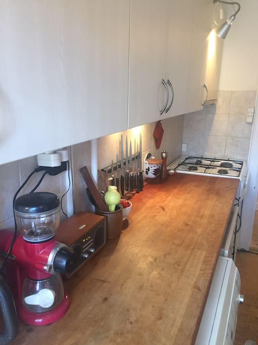 The Kitchen with gas stove, electric oven, coffee grinder, knives et al