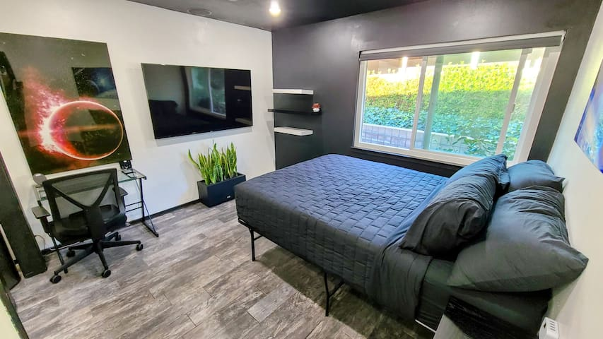 """Guest Room 1. 13"""" thick gel-memory foam mattress, linens and pillows provided not shown. Motorized window shade, 65"""" UDH TV, bookshelf, office chair and desk."""