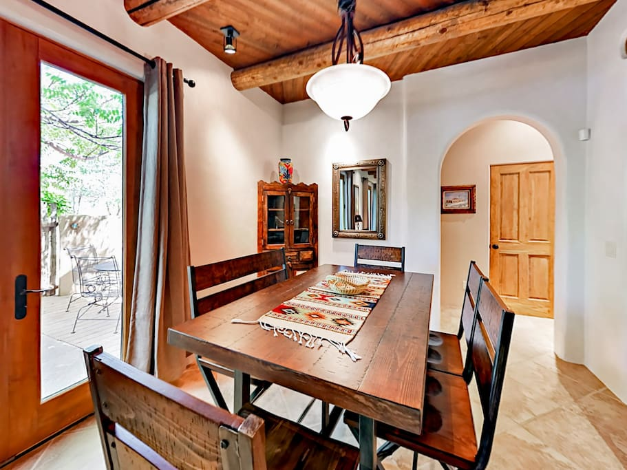 The dining room features a rustic wood table that can comfortably seat 6, as well as direct access to the private courtyard.