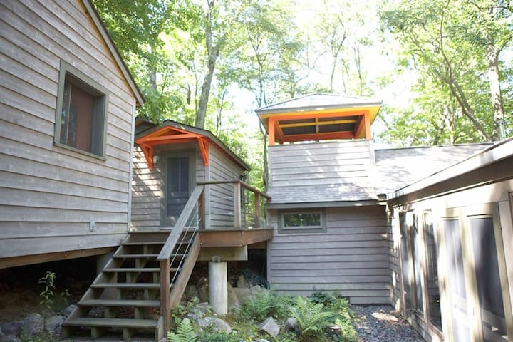 Upper  two cabins and a kids lookout play area attached to the home by steps and a deck with a modern picnic table and benches