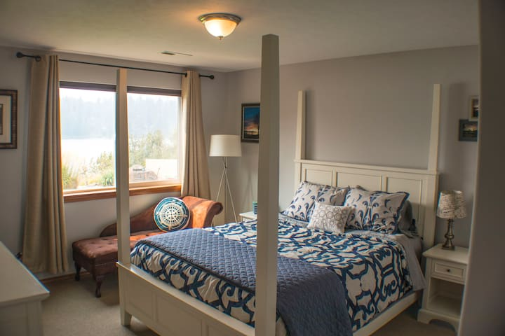 A comfortable poster queen bed with a beautiful lake view in the bedroom.