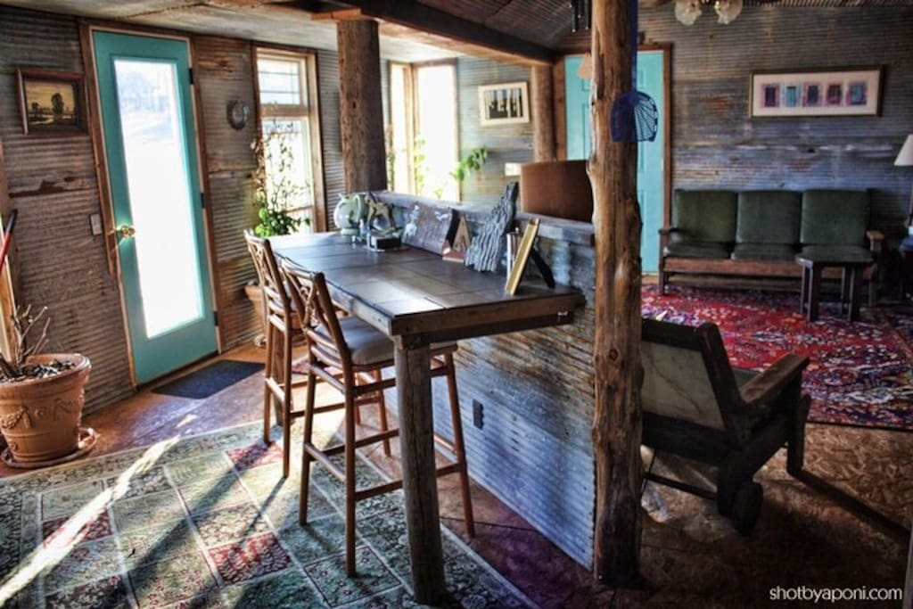 Breakfast bar and living room. Atrium door to your private deck overlooking pastures, hills, and beautiful nighttime starlight views on the left. A family of deer and many other wildlife species make regular cameo appearances.