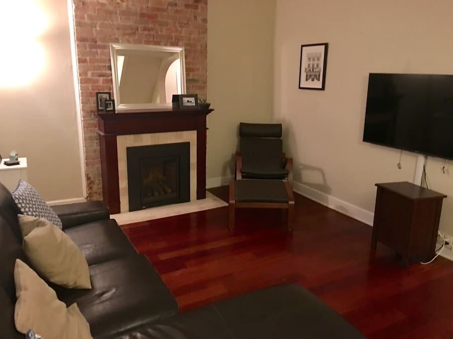 Cozy living room with exposed brick, working gas fireplace, flat screen HD TV, and comfy leather couch.
