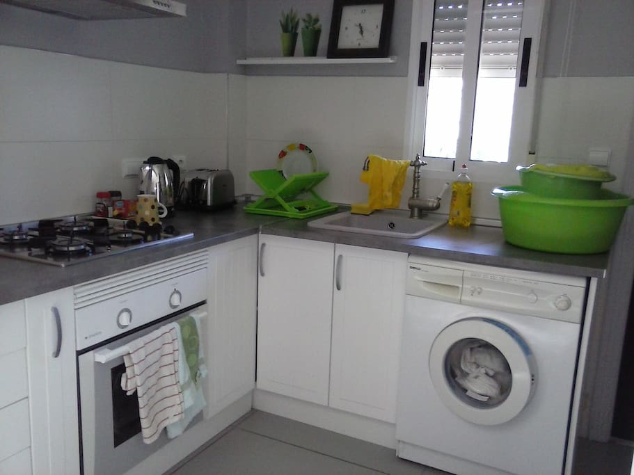 Modern kitchen with gas hob, electric oven, kettle, toaster and washing machine.