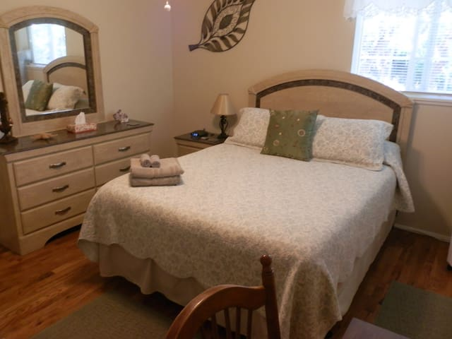 Bedroom with queen size bed,T.V.,air conditioning and desk.