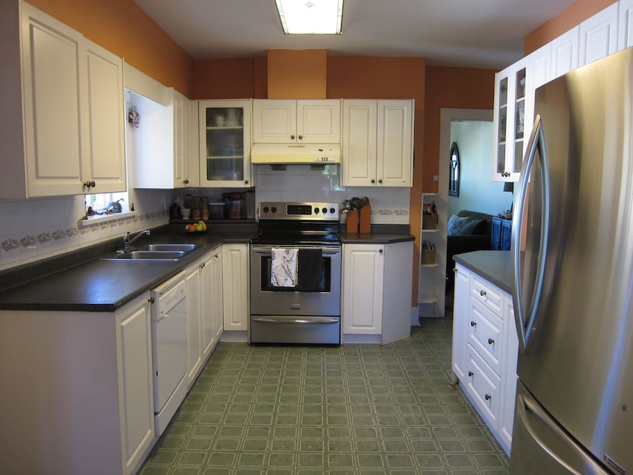 Spacious fully appointed kitchen with dishwasher, refrigerator, range, and microwave.