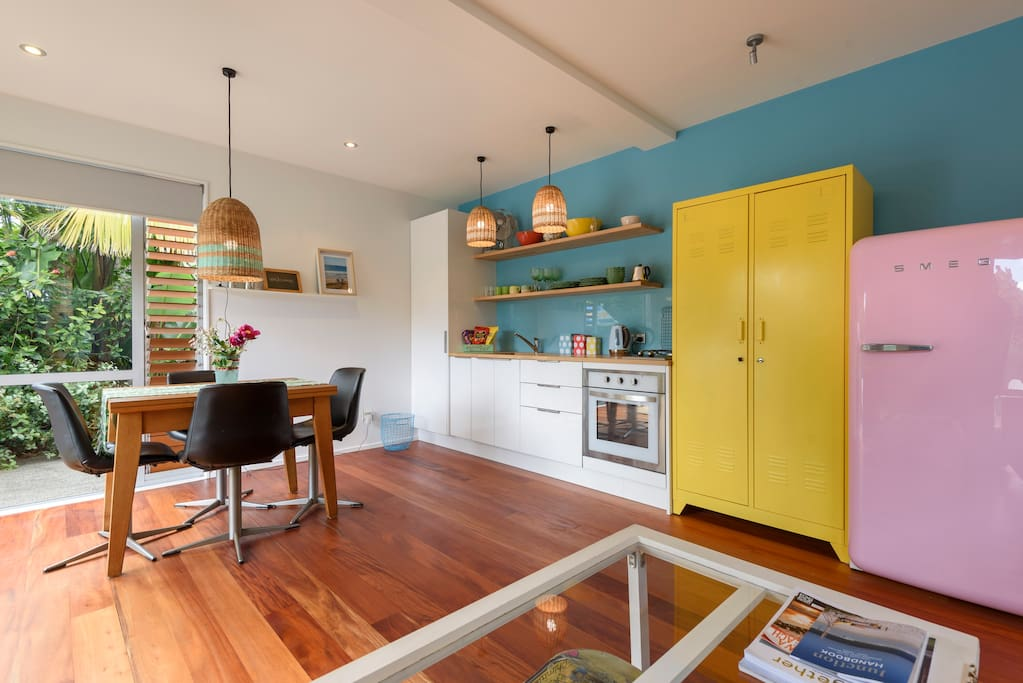 Living area with full stove, Smeg pink refrigerator, funky lights