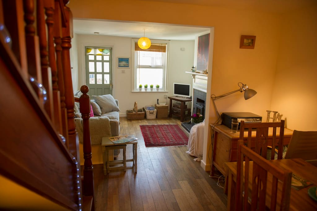 The open plan lounge/dining room has original wooden floors, comfy sofa and log burner.