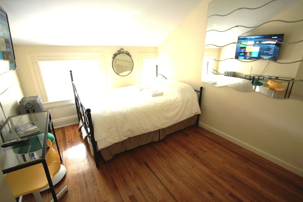 Bedroom 1 furnished with full-sized double bed for 2, 48 inch Roku TV, and personal desk for 2.