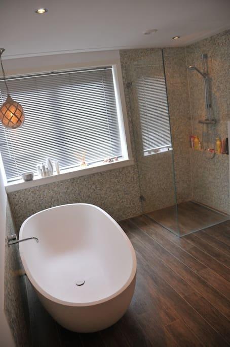 Ruime badkamer met douche, toilet en 2 persoonsbad en vloerverwarming