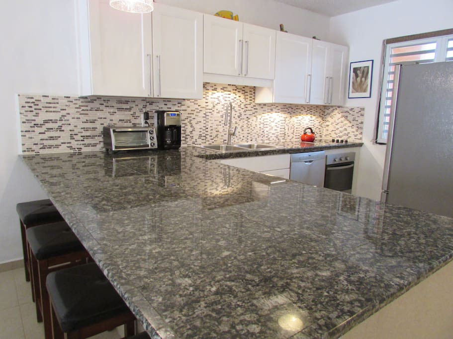 New kitchen with granite counters, rock backsplash, and stainless appliances