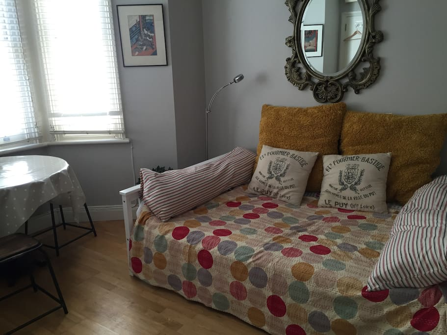 Double bed and table in bay window with three stools