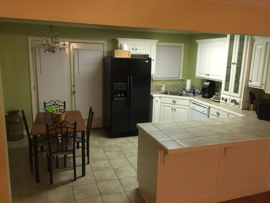 This is an updated photo of the kitchen showing the microwave, coffee pot, fridge and table.