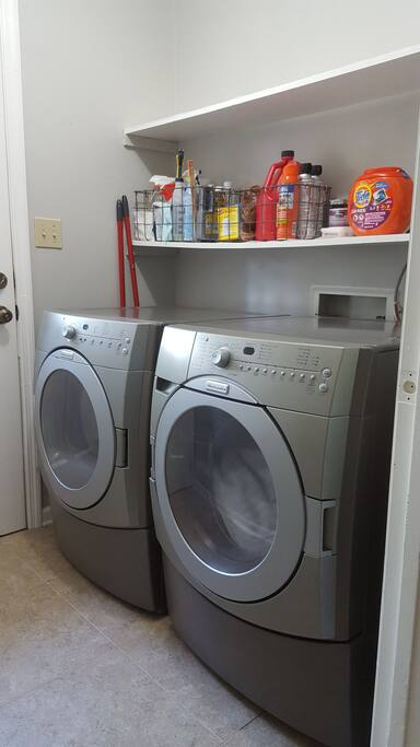 Fully stocked laundry room with Gain dryer sheets, Tide pods, Broom, Dry mop and Iron