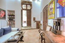 Una bellissima consolle autentica Luigi XIV e un tavolo a bandelle romano in massello di noce accompagnato da due splendide poltrone completano l'arredamento del living room