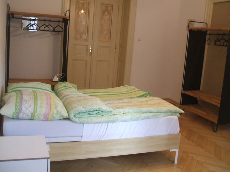 Another view of your private room showing the  double bed, night table, wardrobes, and door to the hallway.