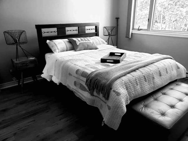 """Rustic Queen bed with pillow top sealy mattress and a leather ottoman.   The large bedroom has a cathedral ceiling with a  large picturesque window, a full size en-suite bathroom, walk-in closet and a LG 43"""" Smart TV"""
