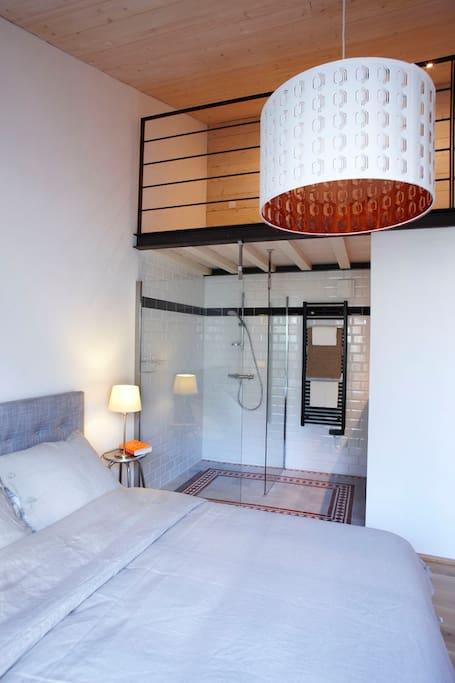 grand lit double 160x200 avec une douche à l'italienne donnant directement sur une terrasse bois et jardin
