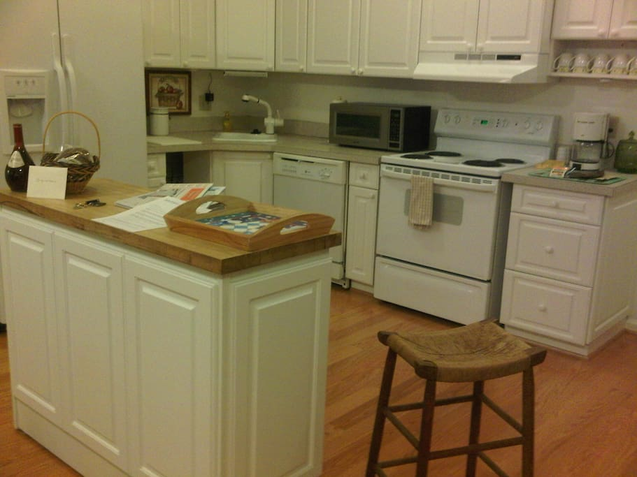 A large, fully-outfitted chef's kitchen with:  side-by-side fridge with ice-and-water in the door, disposal, microwave, and stove with self-cleaning oven plus kitchen utensils, pots and pans, dishes, flatware, glassware, and small appliances.