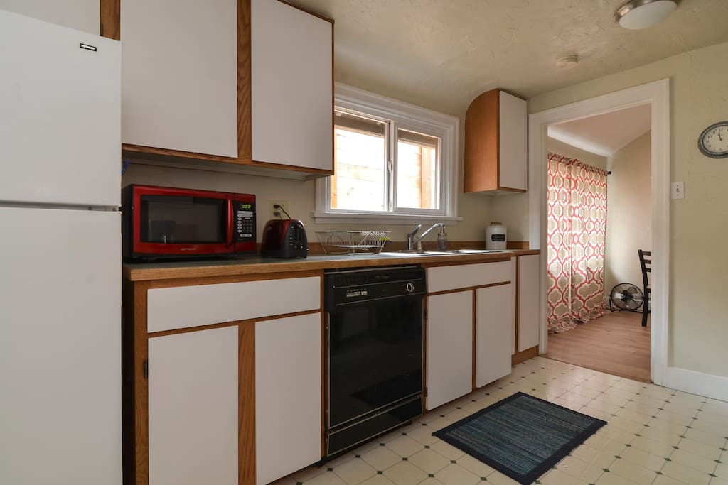 Spacious kitchen with a full sized gas range, dishwasher, warm lighting, modern comforts and quality dishes and cooking tools.