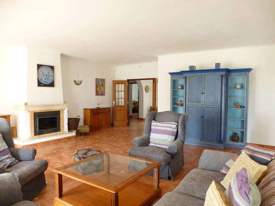 Large open plan living room with wood burning fire,  two seating areas, TV unit and pool table.