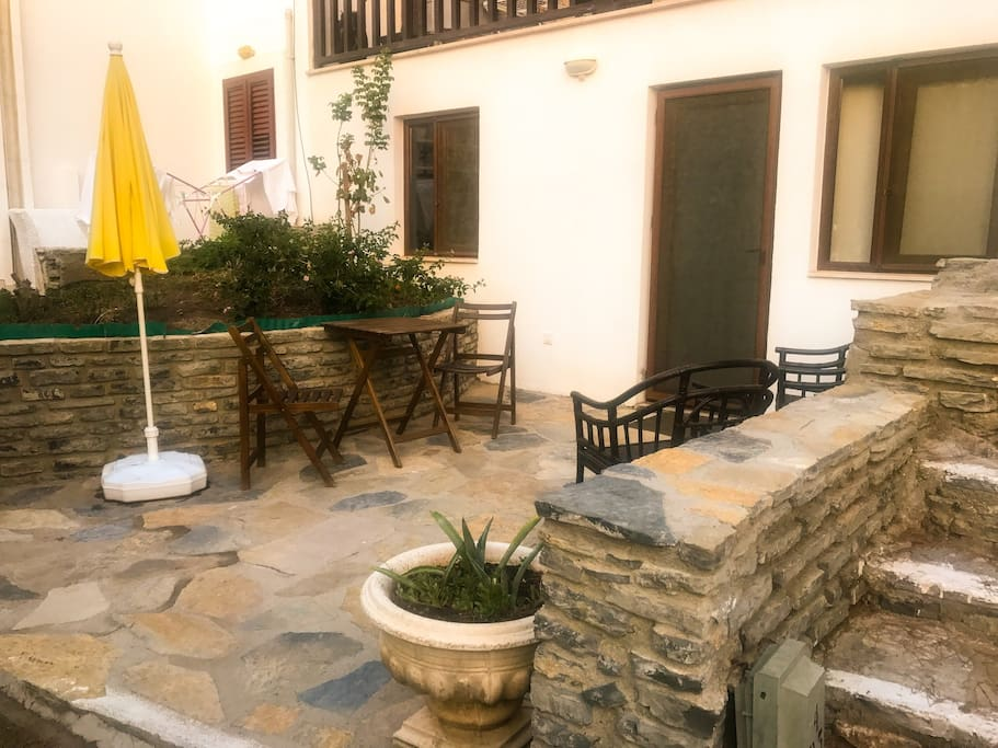 Entrance of apartment in private garden with umbrella, 2 easy chairs, 2 dining chairs and table.