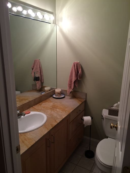 The bathroom has plenty of counter space, good lighting, and a full size tub/shower.