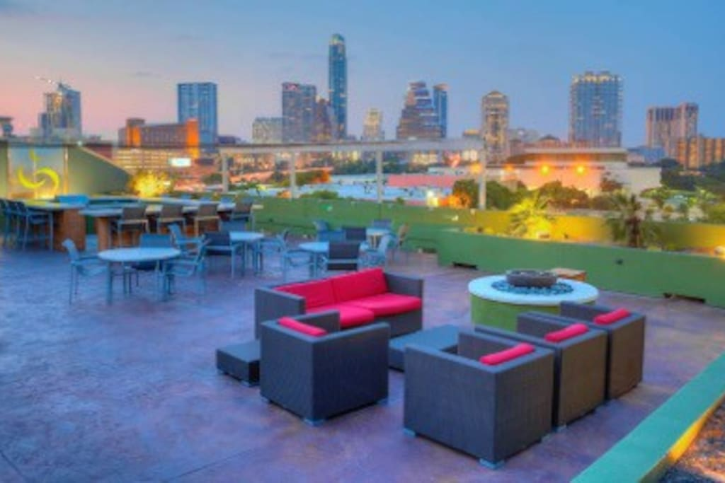 Rooftop with plasma TVs, a grill, bar counter, fire pit, and incredible skyline view of the city!