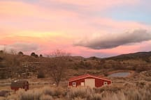 The view from the Airstream deck at sunset includes the barn, the lake, and views of the mountains all the way to Wrightwood, which is 13 miles East of the ranch.