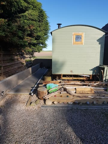 Front of shepherds hut and guest parking infront of accommodation.