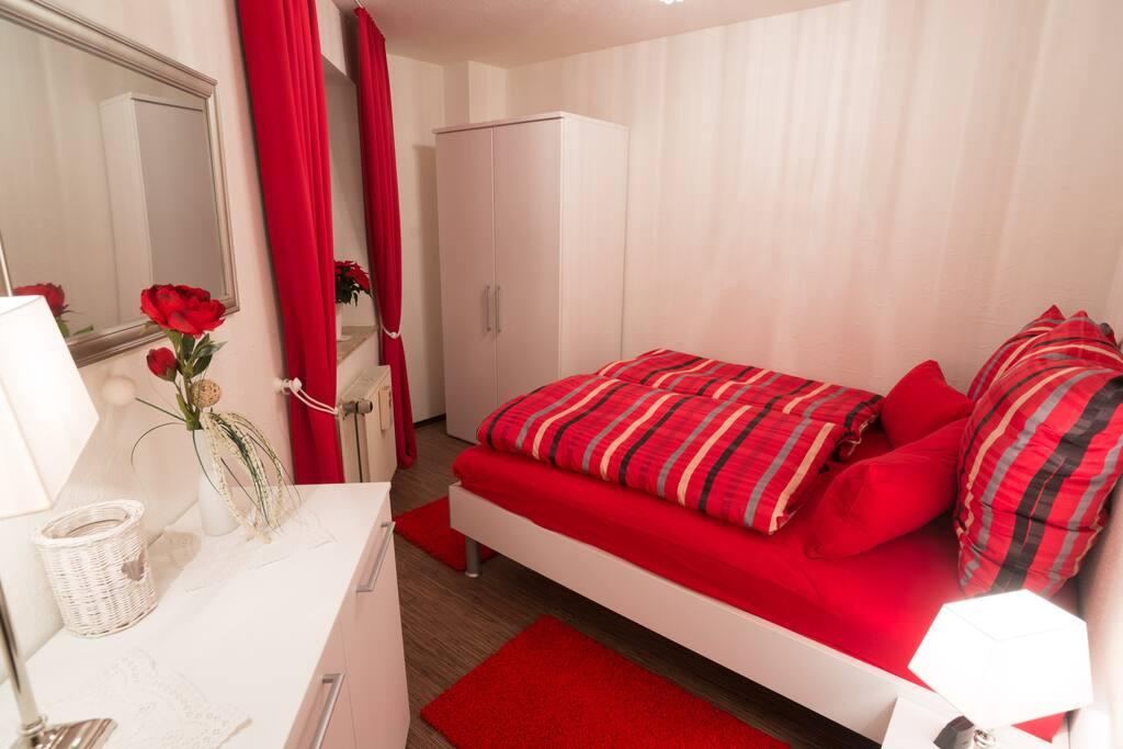 Schlafzimmer Doppelbett, 1 Nachttisch, Kleiderschrank, Kommode; Blick vom Wohnzimmer