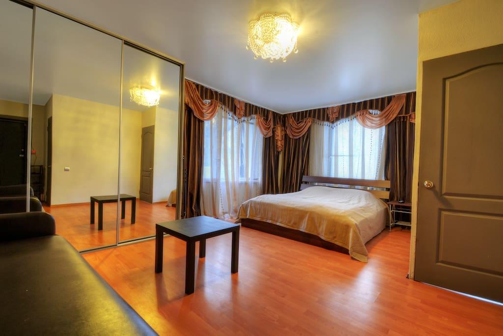 Приятную обстановку создают большая двуспальная кровать, качественный домашний текстиль и красивая люстра.