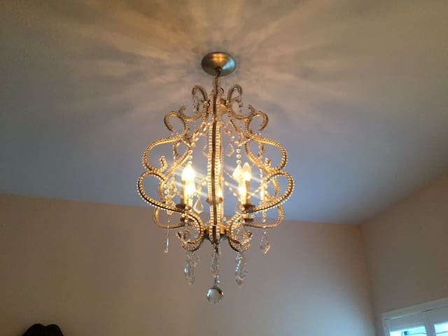 The golden crystal chandelier adds an elegant touch and can be adjusted for brightness.