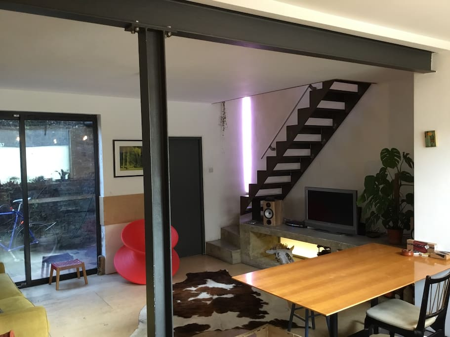 Open plan space with steel beams, brutalist concrete features, suspended staircase and huge oak dining table