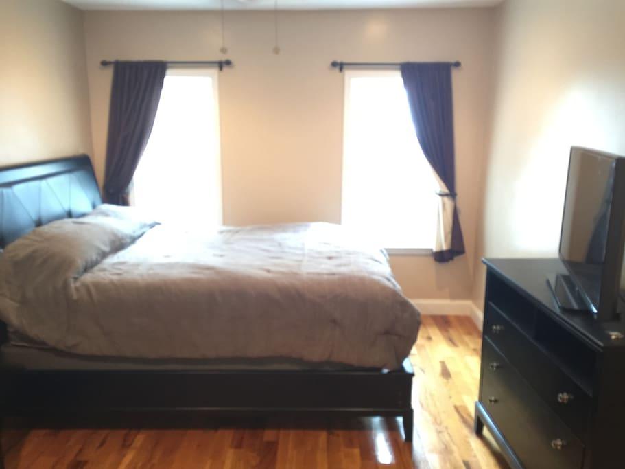 Master bedroom with queen bedroom, dresser and HDTV.