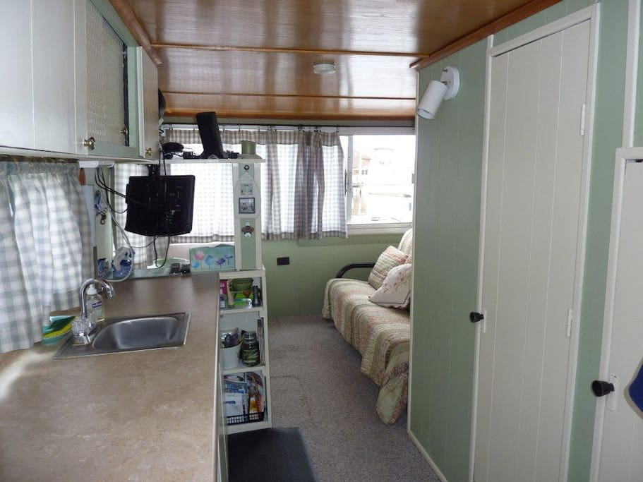 Cozy and polished, lower living and sleeping quarters..Galley W/ small refrigerator on left, Air conditioned .T.V. was intentionally eliminated  to assure  you enjoyment aboard.