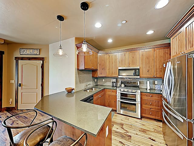 Granite countertops, stainless steel appliances, and wood floors outfit the sleek kitchen.