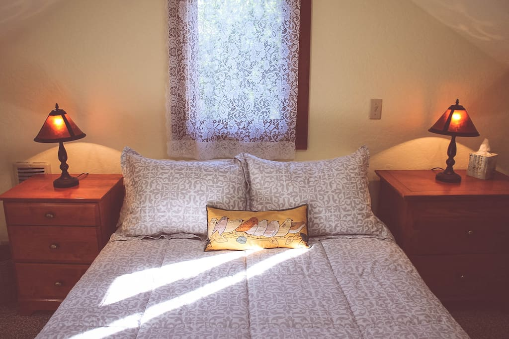 Full sized bed in a cozy loft.