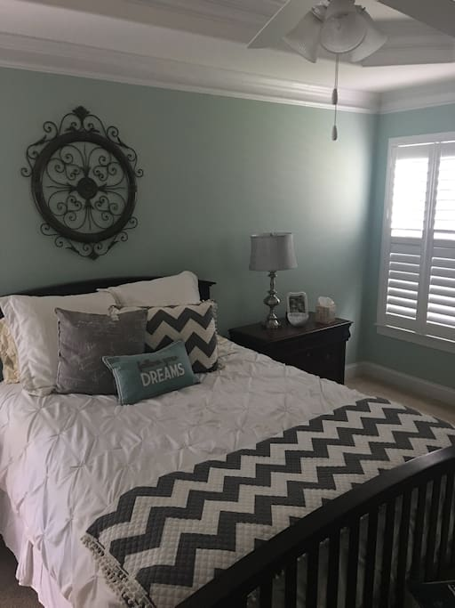 Master bedroom with queen bed on  opposite side of home from the other two bedrooms. Quiet and cozy with ceiling fan and wood shutters