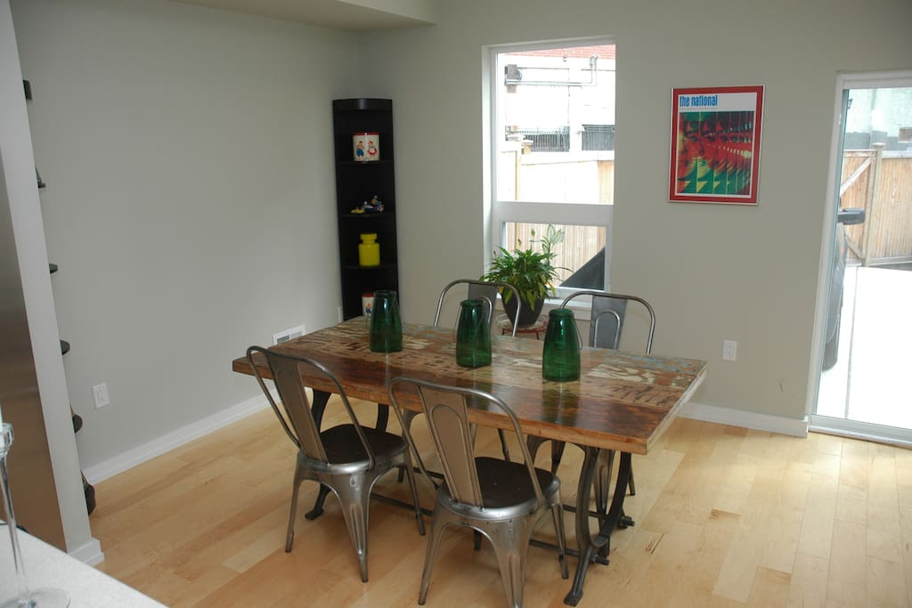 Dining area in kitchen. Looks out on patio, fenced driveway. BBQ by patio doors.