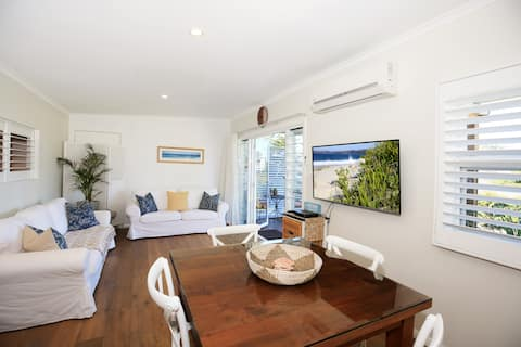 Lovely living area with double sofa bed and doors opening onto deck..