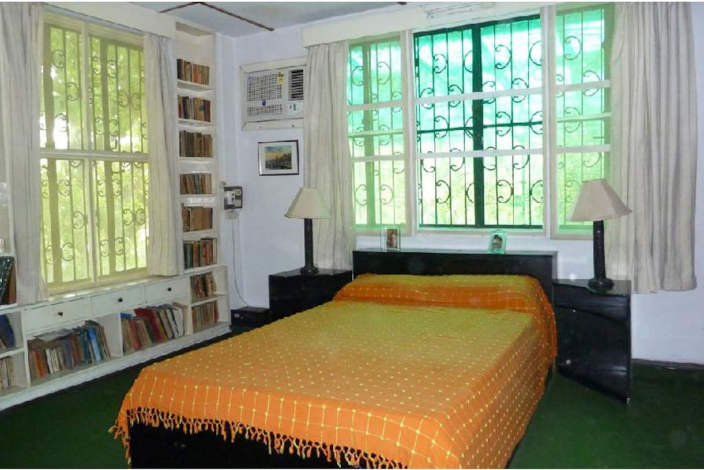 The Green room is on the first floor and the  large windows overlook Mango and Laburnum trees.