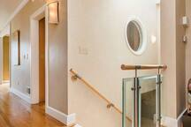 Stairway from main living area down to entrance hall and laundry room.